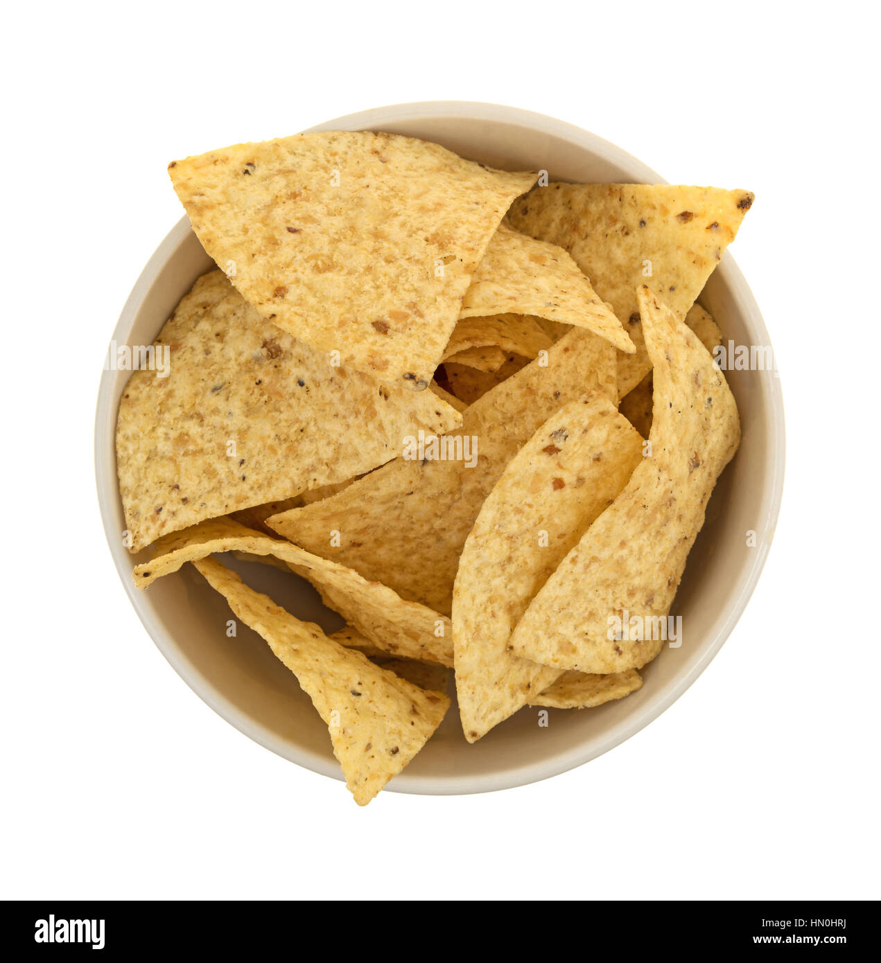 Top view of a bowl filled with crispy tortilla chips isolated on a white background. - Stock Image