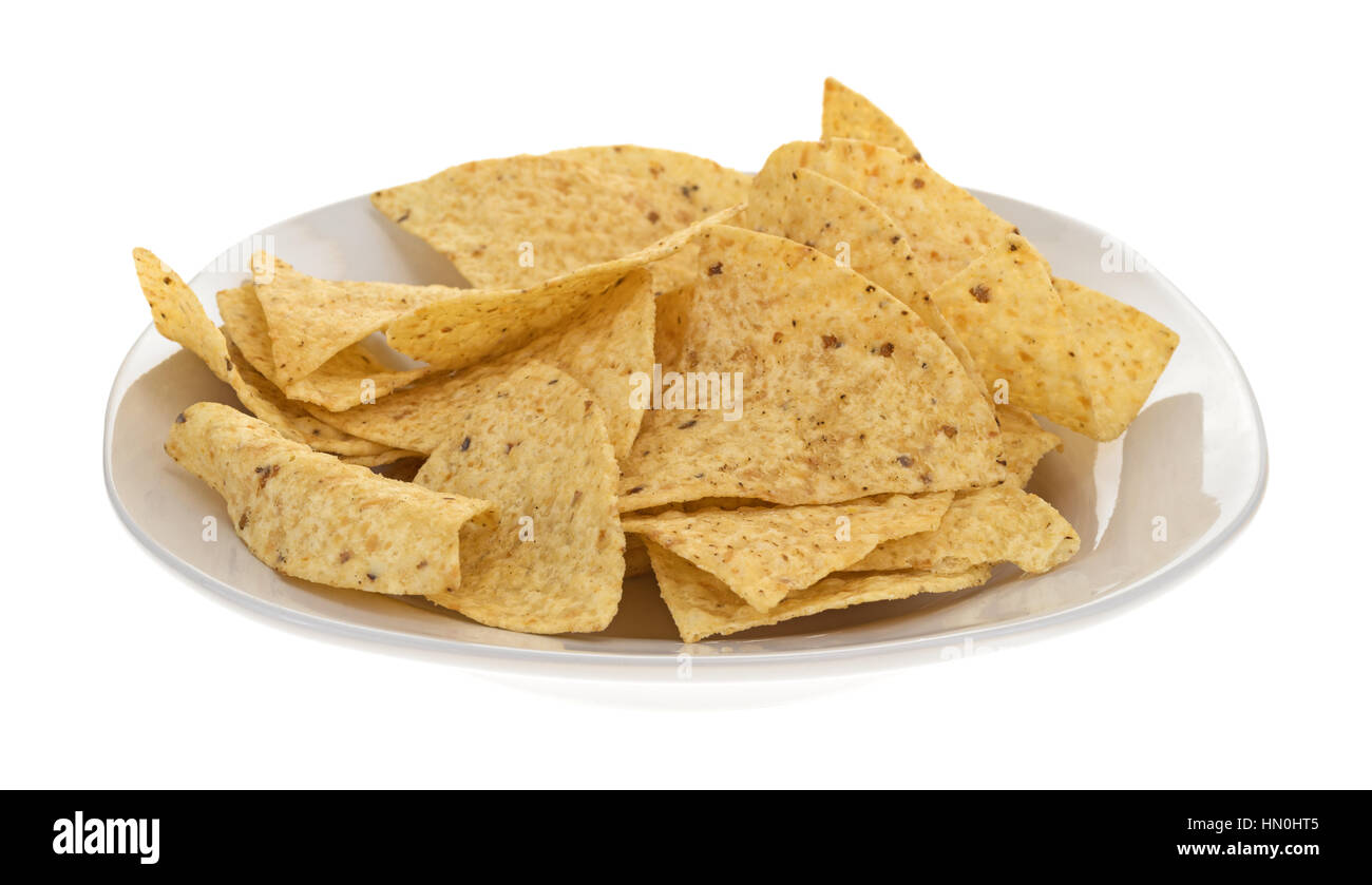 Side view of a plate with crispy tortilla chips isolated on a white background. - Stock Image