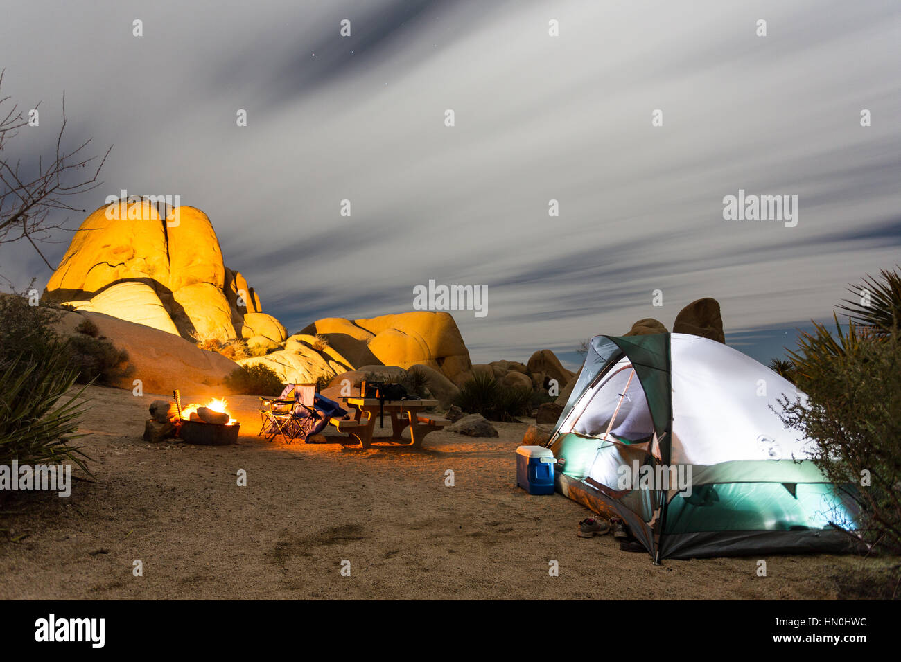 A tent sits next to a campfire at night in a Joshua Tree National Park campsite. - Stock Image