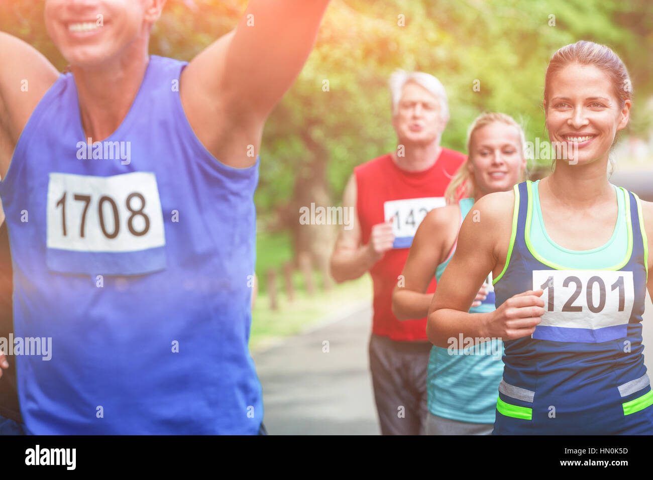 Marathon male athlete crossing the finish line in park - Stock Image