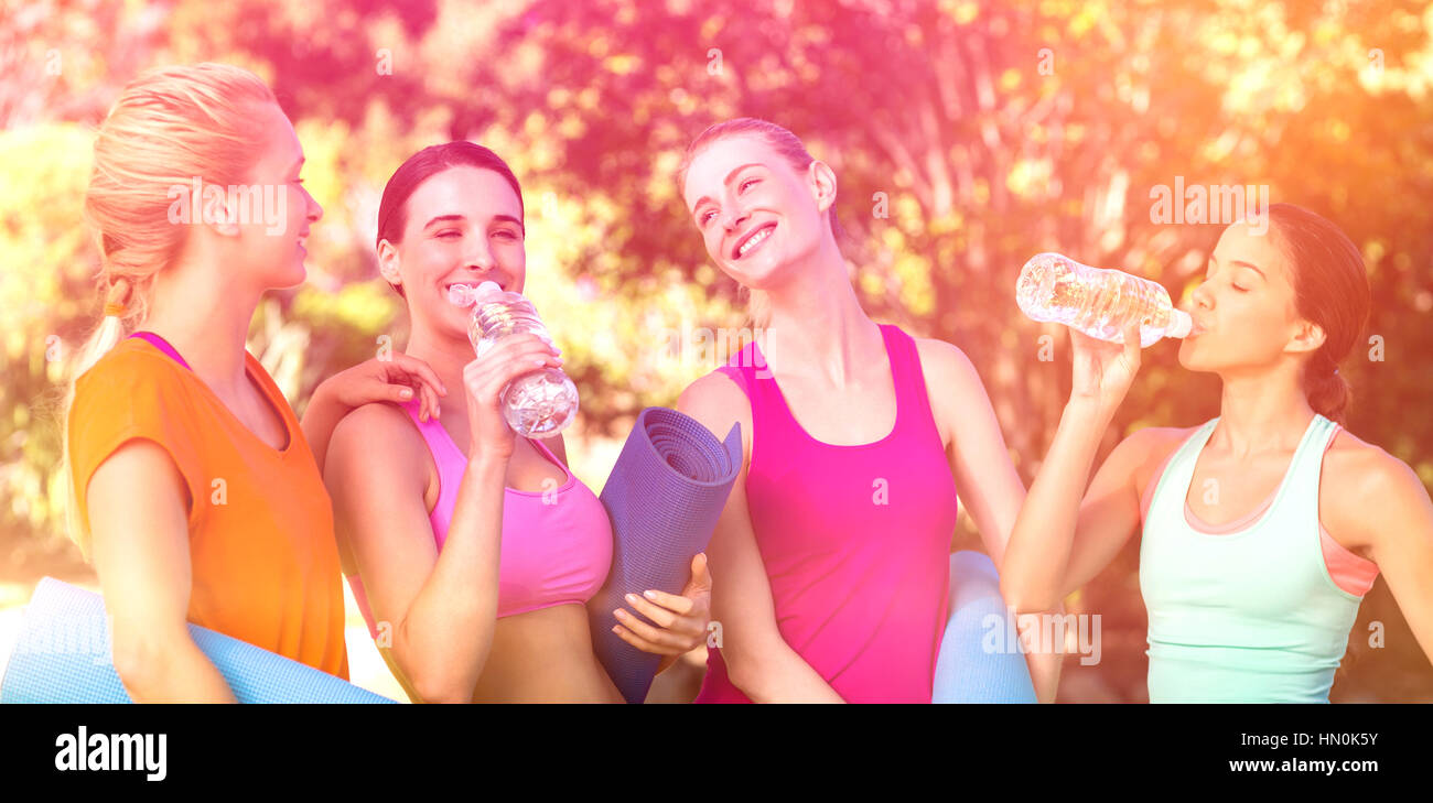 Beautiful women holding exercise mat after workout in park - Stock Image