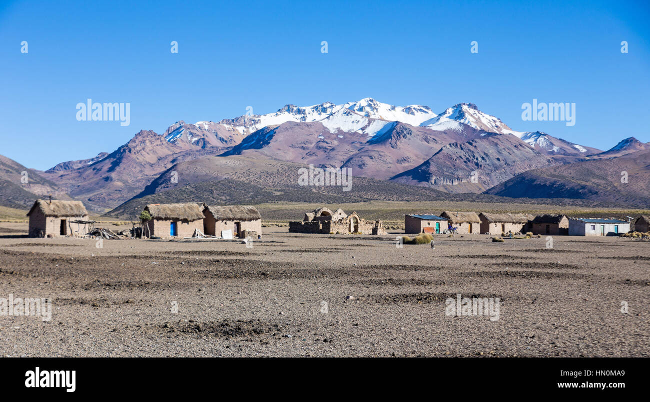 Small village of shepherds of llamas in the Andean mountains. High Andean tundra landscape in the mountains of the - Stock Image