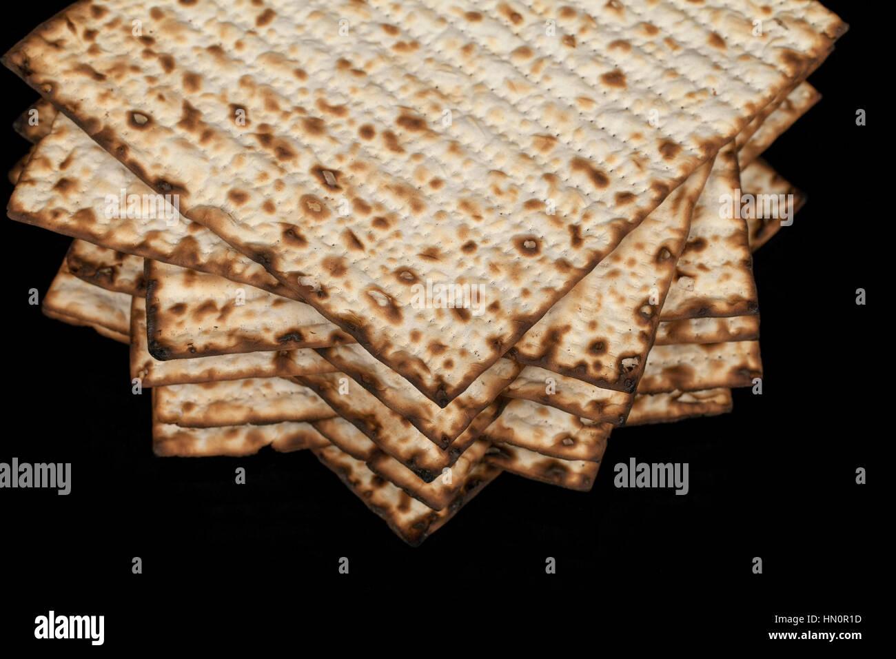 Traditional Jewish matzah on a black background. Close-up - Stock Image