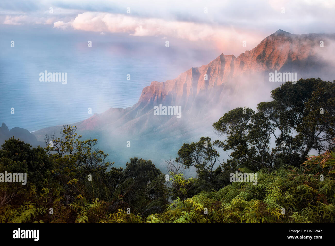 Last light and parting fog reveals the mystical Kalalau Valley along the Na Pali Coast on Hawaii's Island of Kauai. - Stock Image