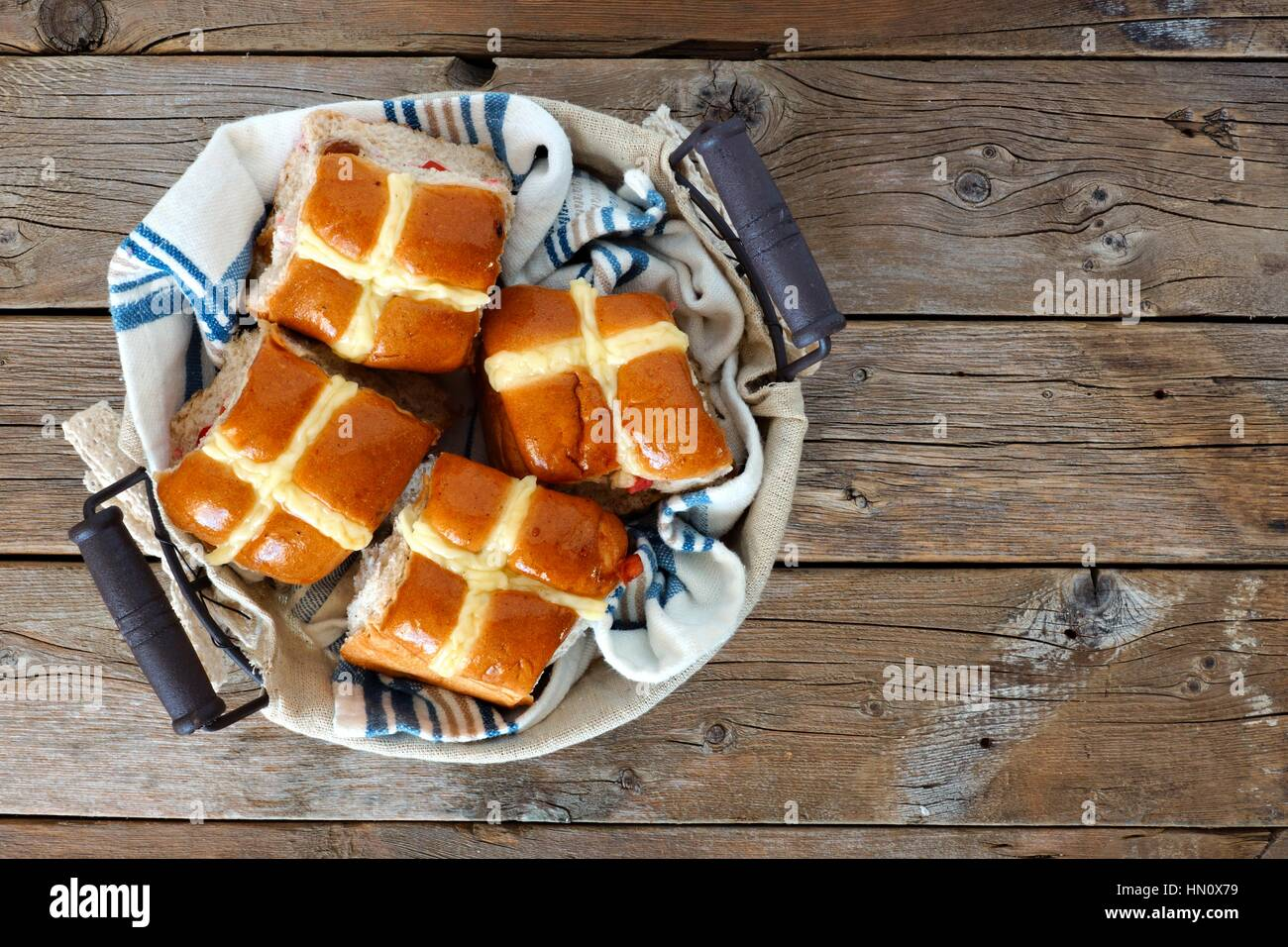 Easter Hot Cross Buns in a basket, downward view on a rustic wood background - Stock Image
