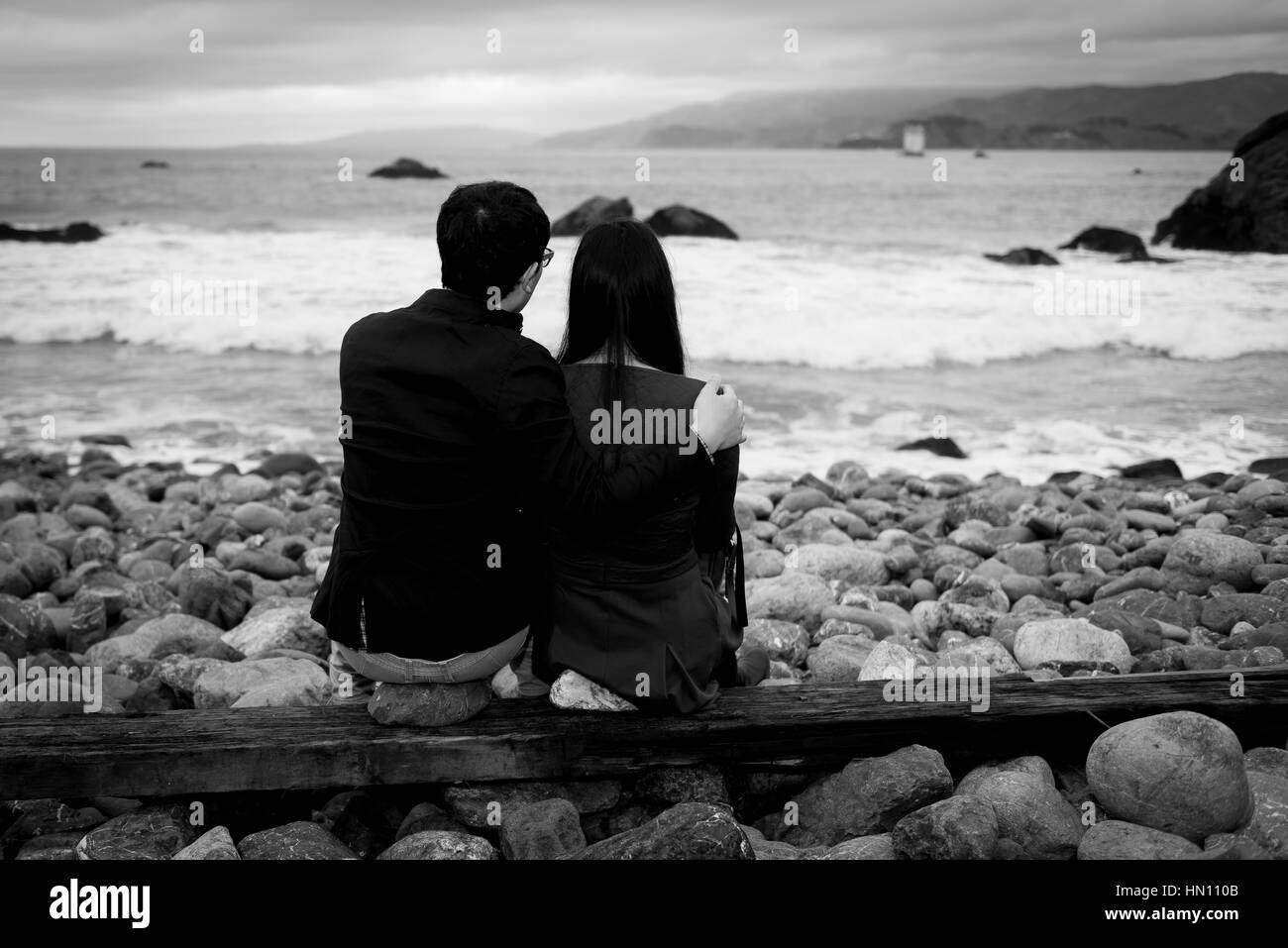 Couple honeymoon sitting on the beach black and white from behind - Stock Image
