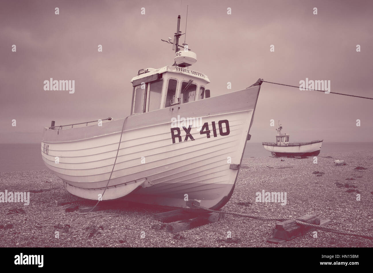 Boats on the shingle beach at Dungeness, Kent, England, UK - Stock Image