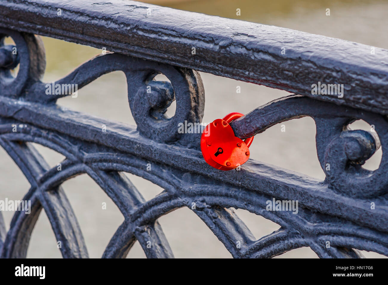 Red padlock fixed to the black rough metal parapet of the bridge over the river as a wedding tradition as a token - Stock Image
