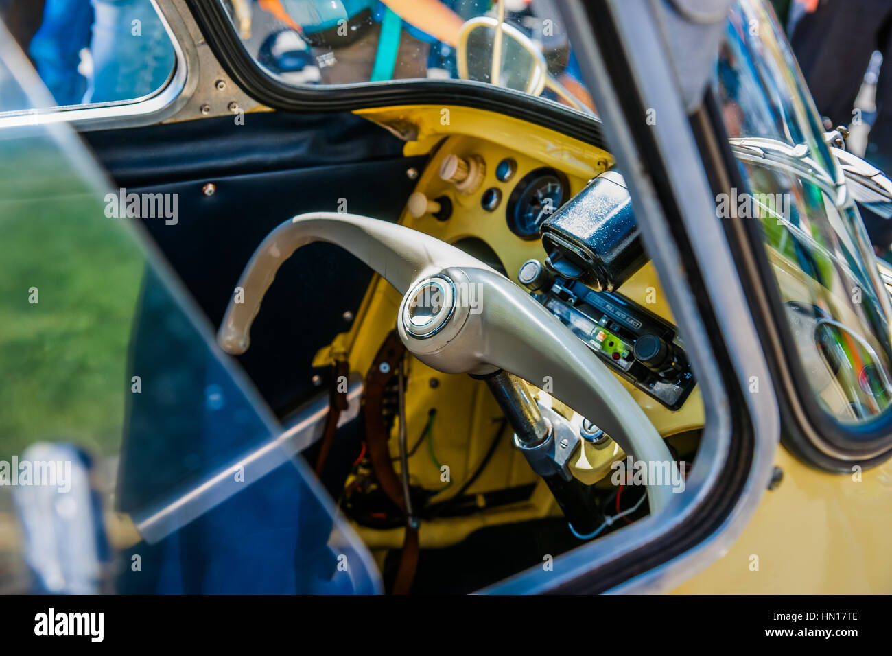 Color and beauty of vintage cars. Steering wheel and an interior of an old European two seater hybrid car-bike. - Stock Image