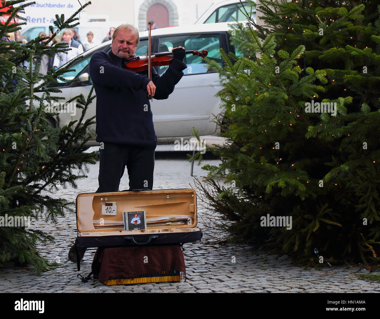 Christmas markets in Europe are an annual celebration with a busker playing his violin for tourists. - Stock Image