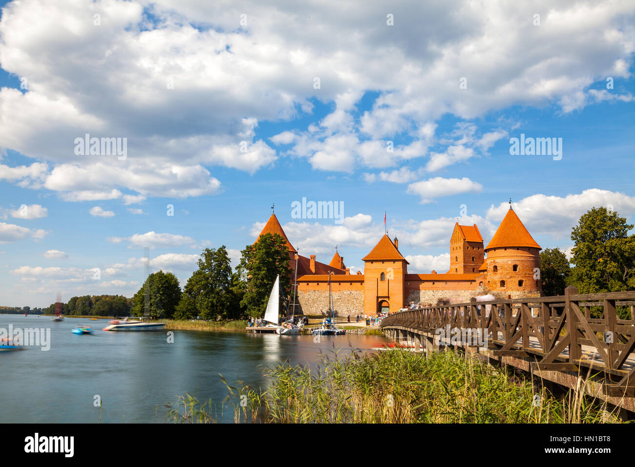 Tourists visit Trakai castle in sunny siummer day, nice time to have boat trip. Long exposure, motion blur Stock Photo