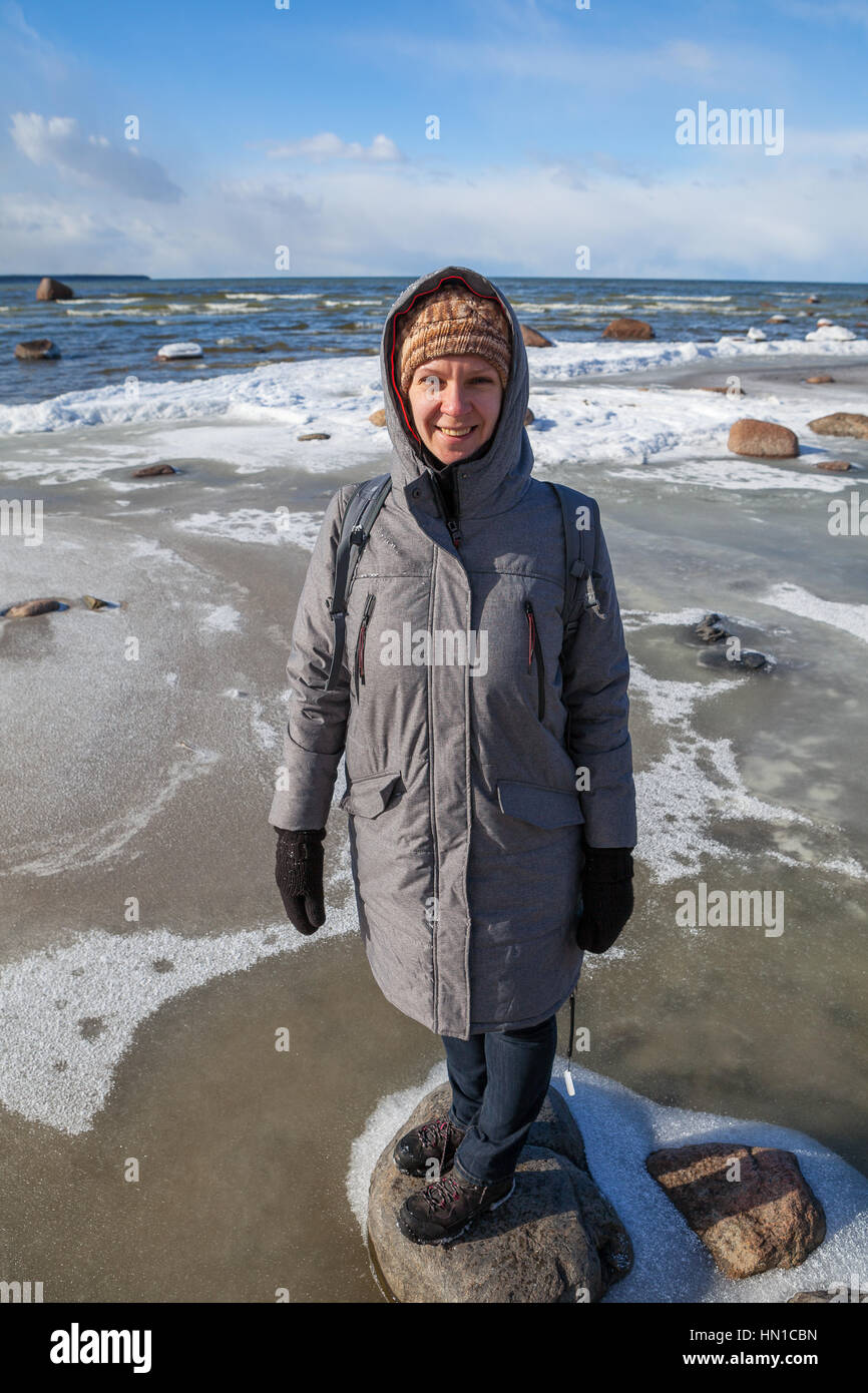 Young smiling woman on the cold and sunny day staying on stone. Coast of Baltic sea - Stock Image