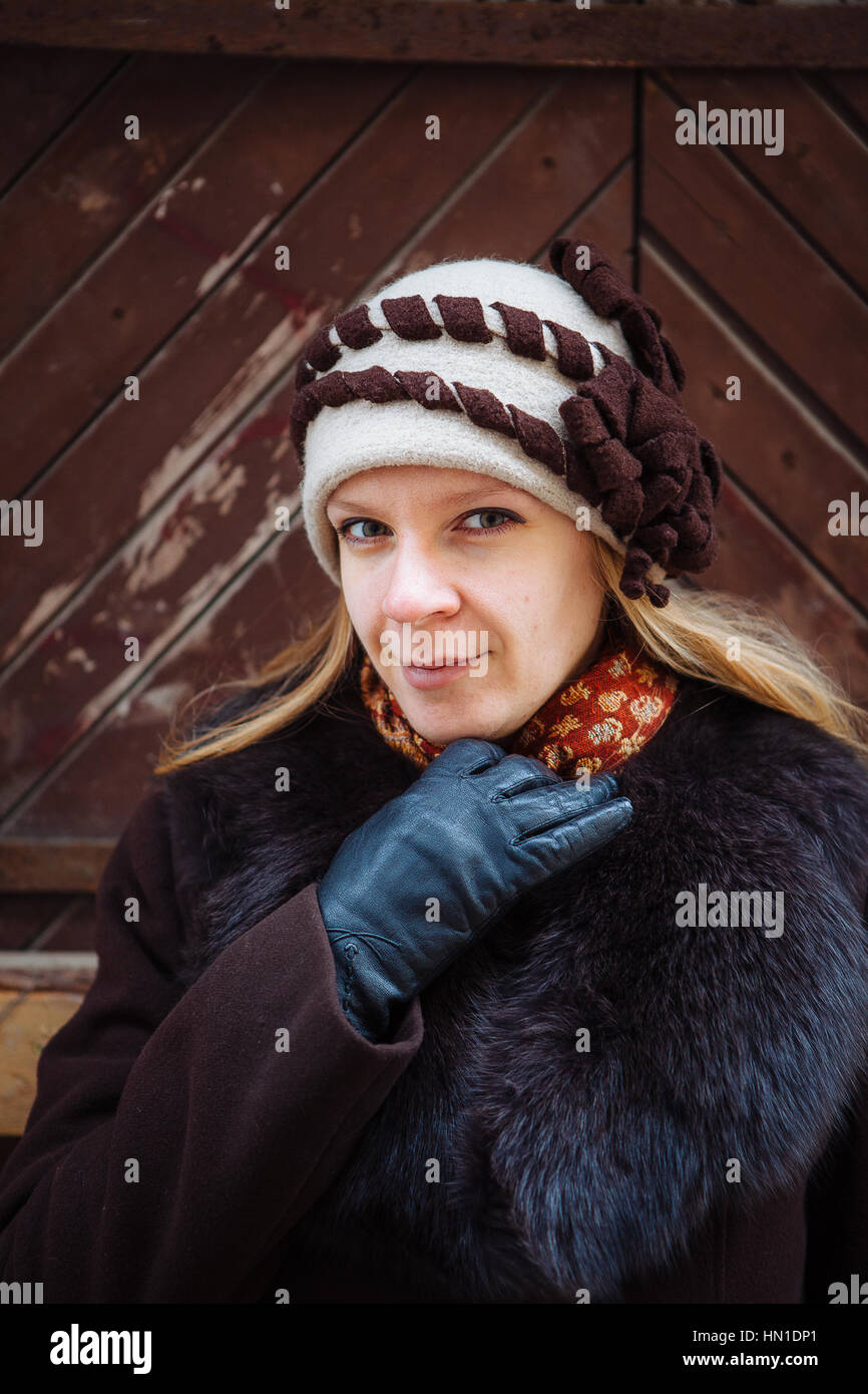 0d0cfec389602 Young woman winter portrait with hat, brown coat and black leather gloves,  outdoor -