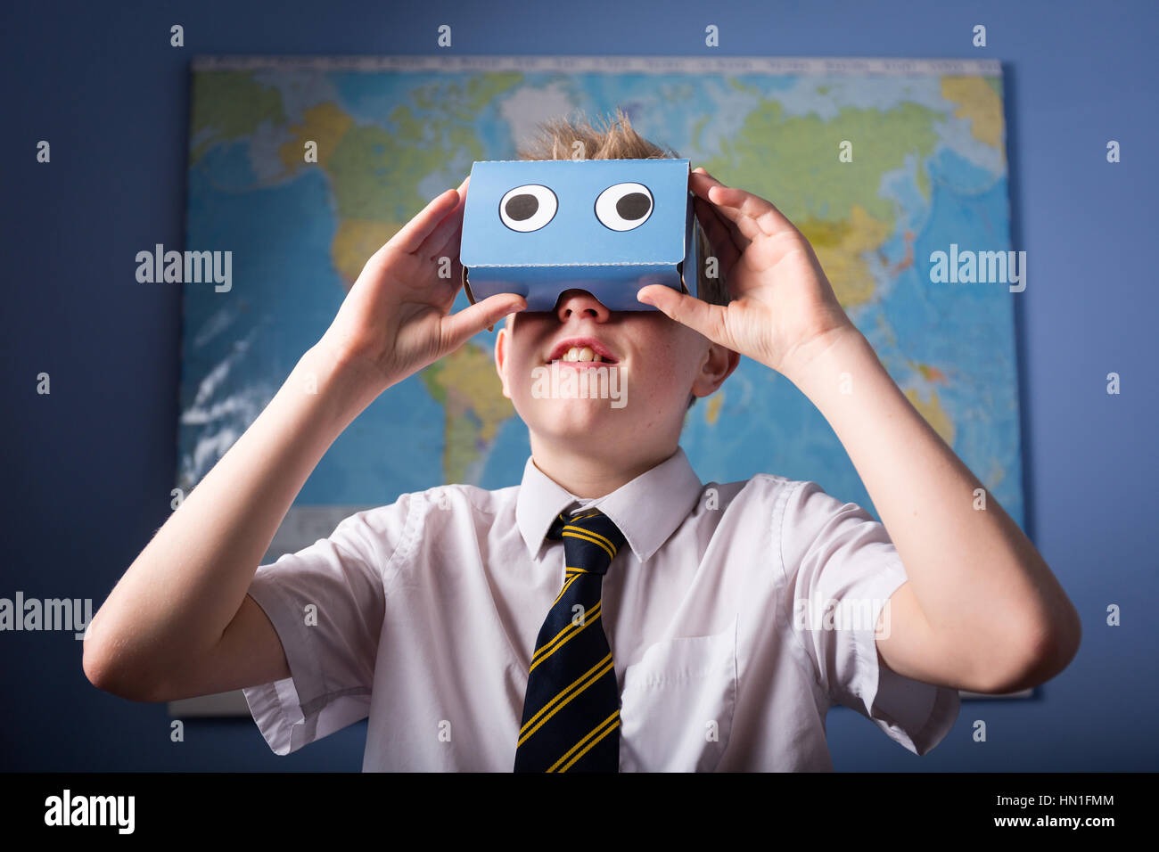 A School Pupil exploring the world through a VR Virtual Reality headset - Stock Image