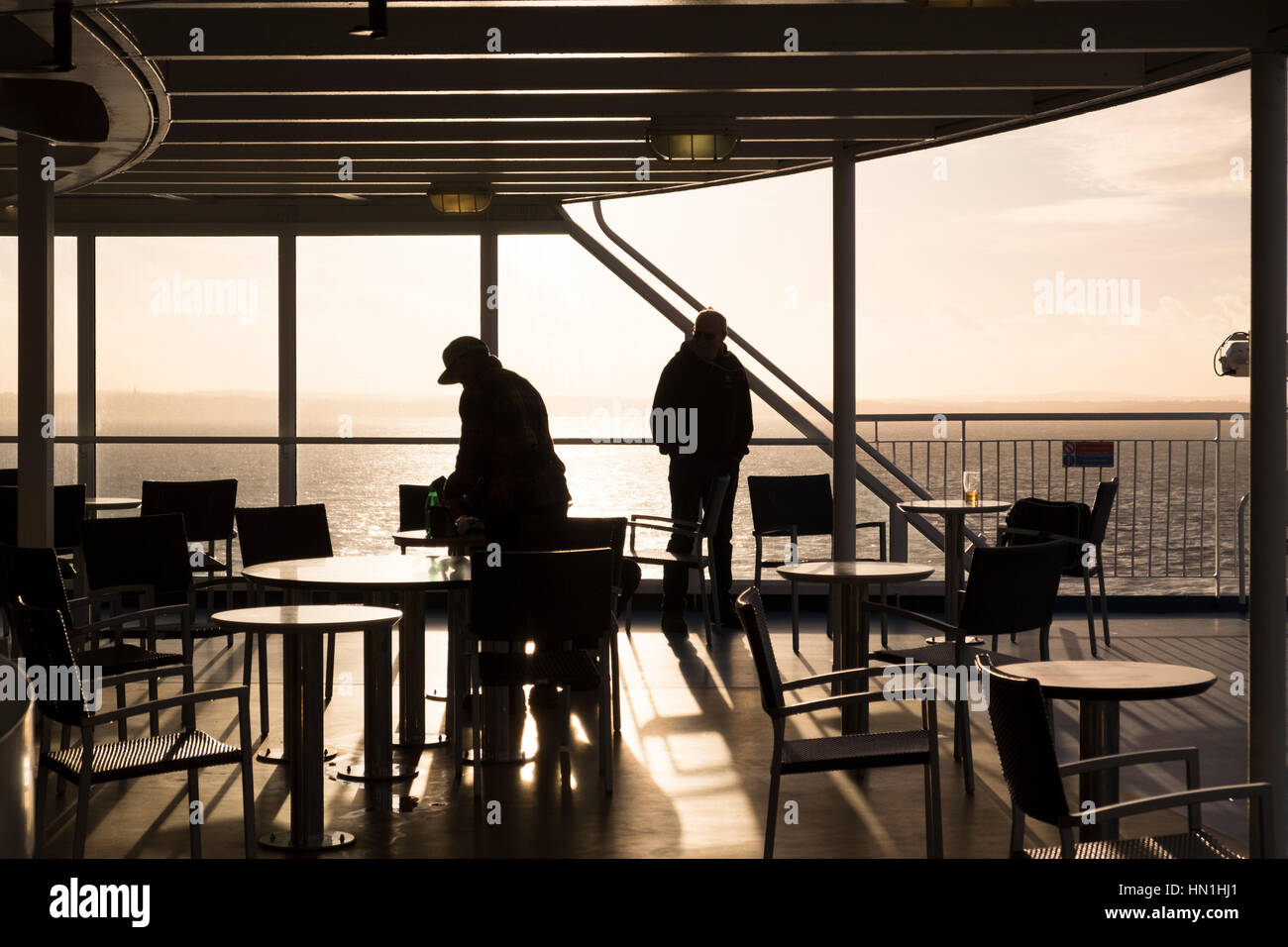 Silhouettes of people tables and chairs on the deck of a small ship - Stock Image