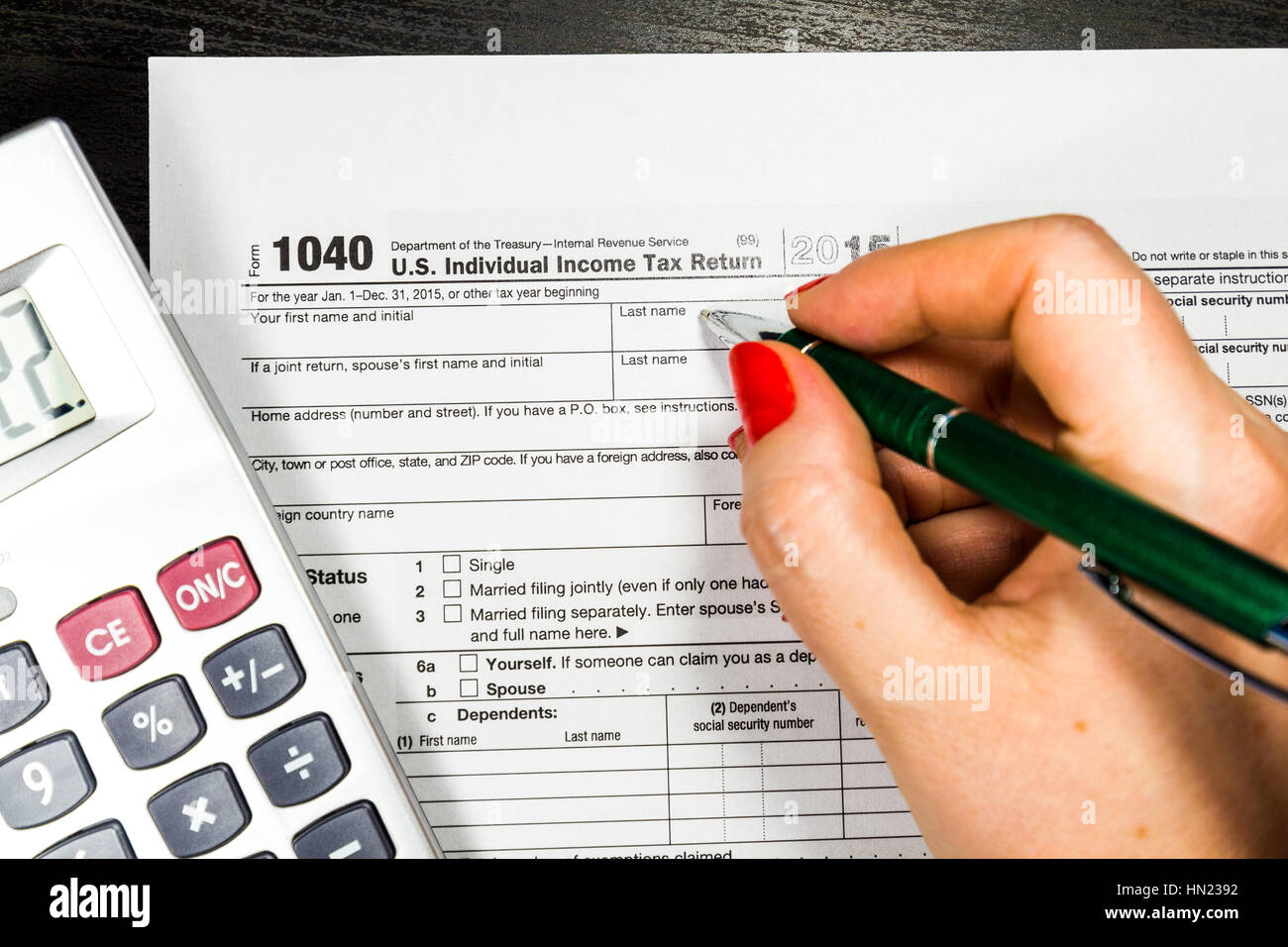 form 1040 calculator  Business woman fills the tax form 12 with pen and ...