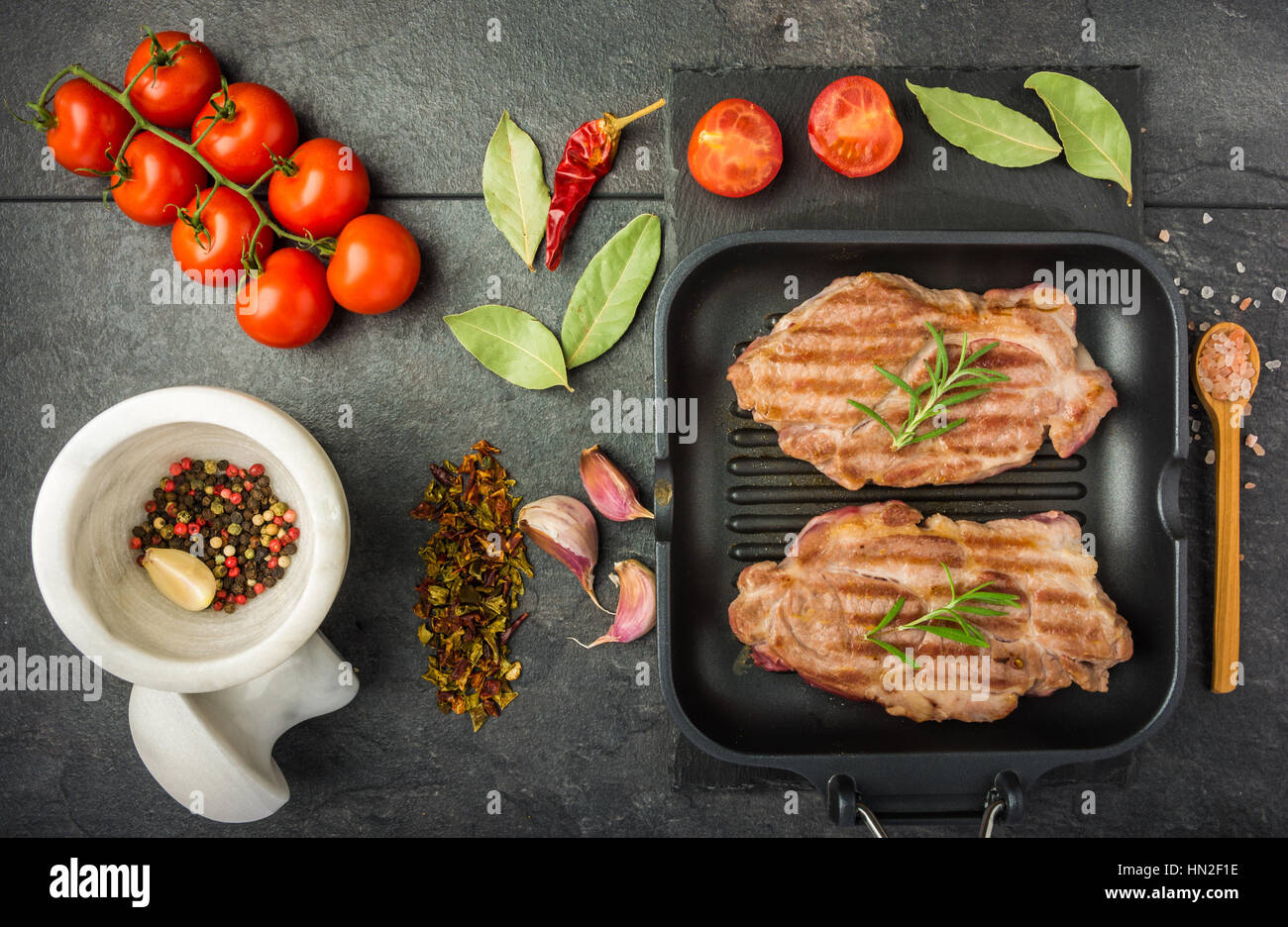 steak with spices and tomatoes cooked on the grill pan on a dark table top view Stock Photo