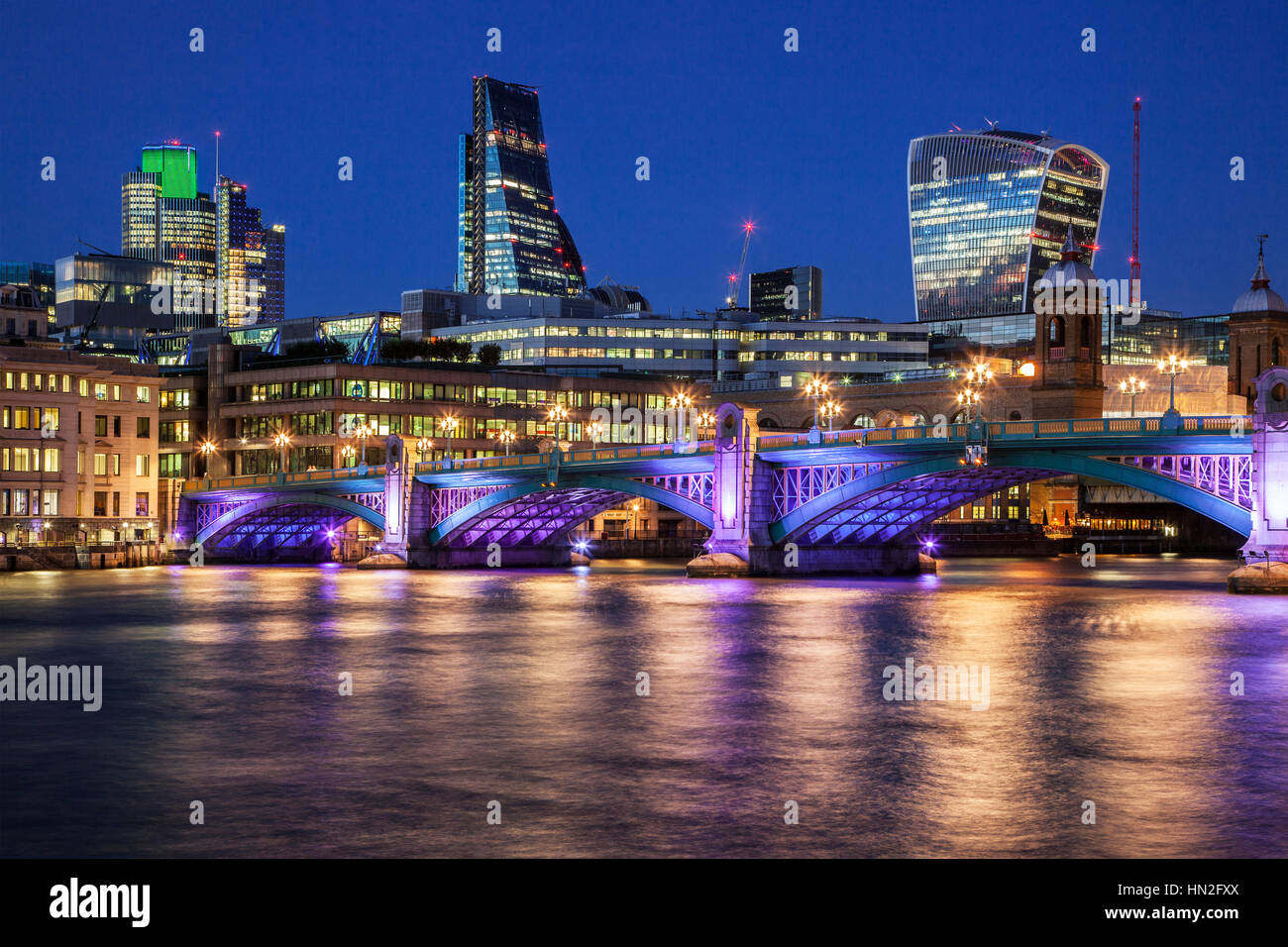 Night time on the River Thames at Southwark Bridge in London with the 'Cheesegrater' and 'Walkie Talkie' - Stock Image