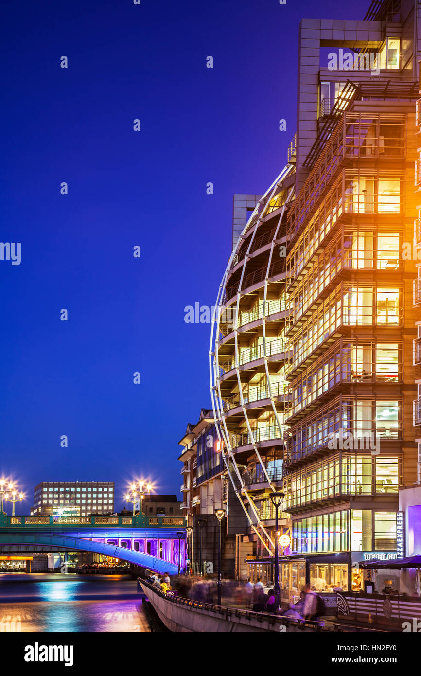 Part of Southwark Bridge and Bankside along the river Thames in London at night. - Stock Image