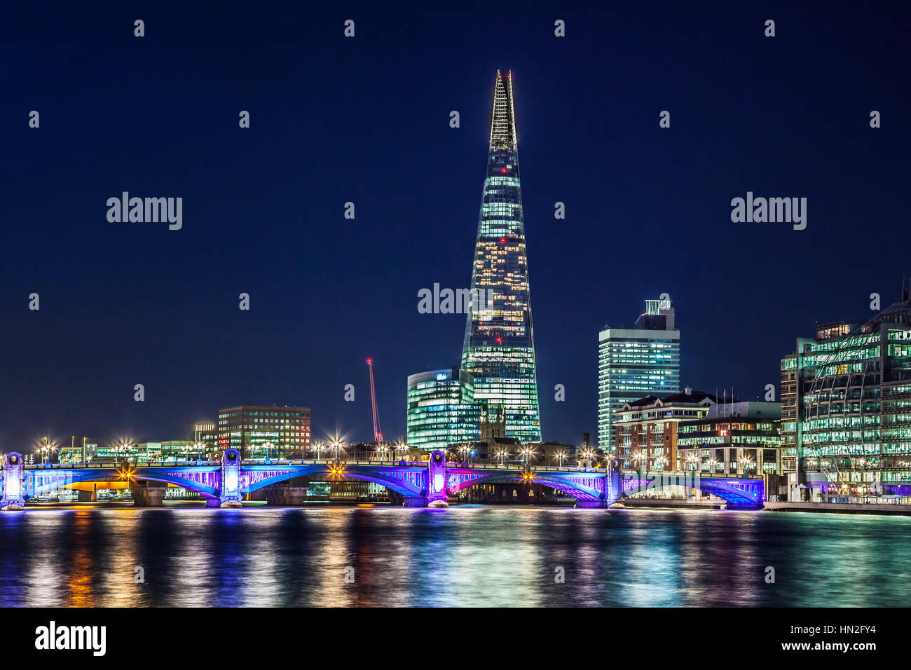 View of the river Thames towards Southwark Bridge and the Shard at night. - Stock Image
