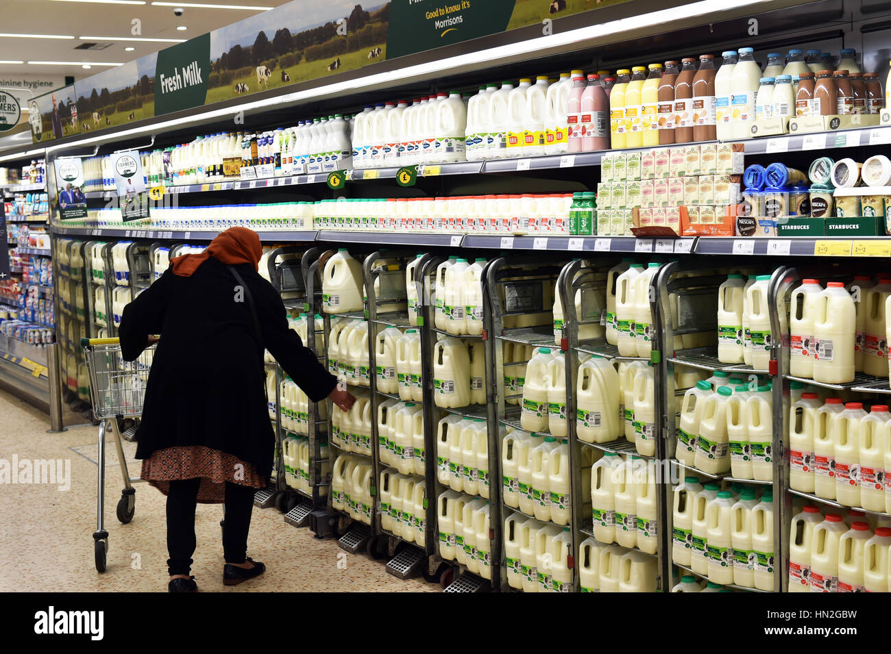 Woman buys milk from the supermarket UK - Stock Image