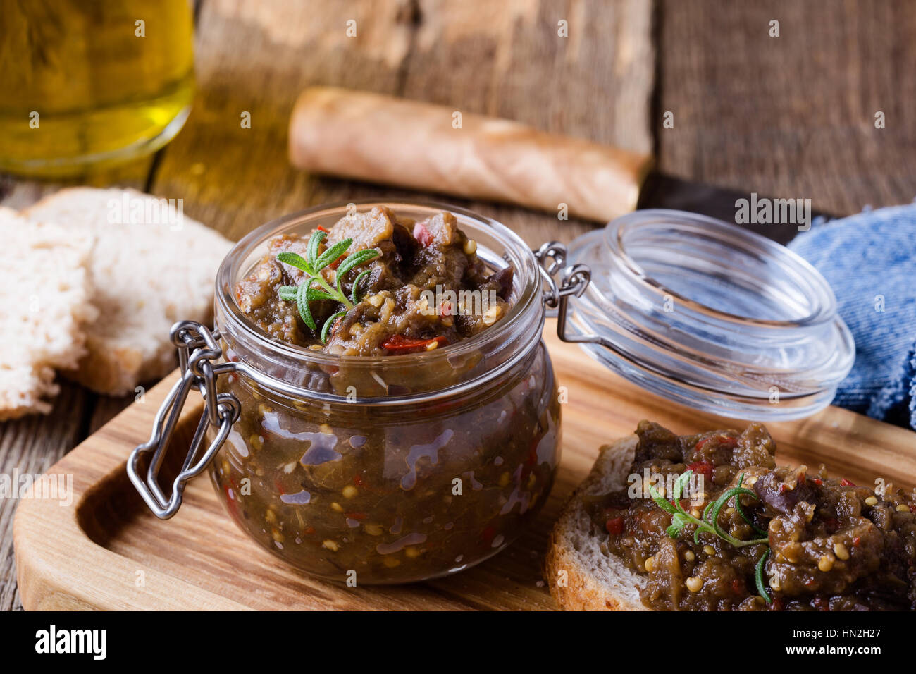Homemade pate of eggplant. Paste in glass jar on rustic wooden table. Useful and healthy vegetarian food - Stock Image