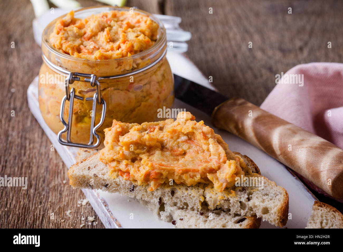 Homemade bean paste, Sandwiches with vegan pate on whole wheat bread. Dip of white beans in glass jar on rustic Stock Photo