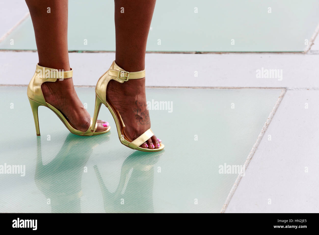 ce179666b76 Legs of Beautiful African American woman in golden high heels shoes ...