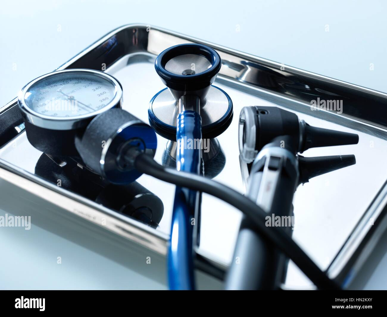 Close-up of a sphygmomanometer, stethoscope and otoscope on a metal tray. - Stock Image