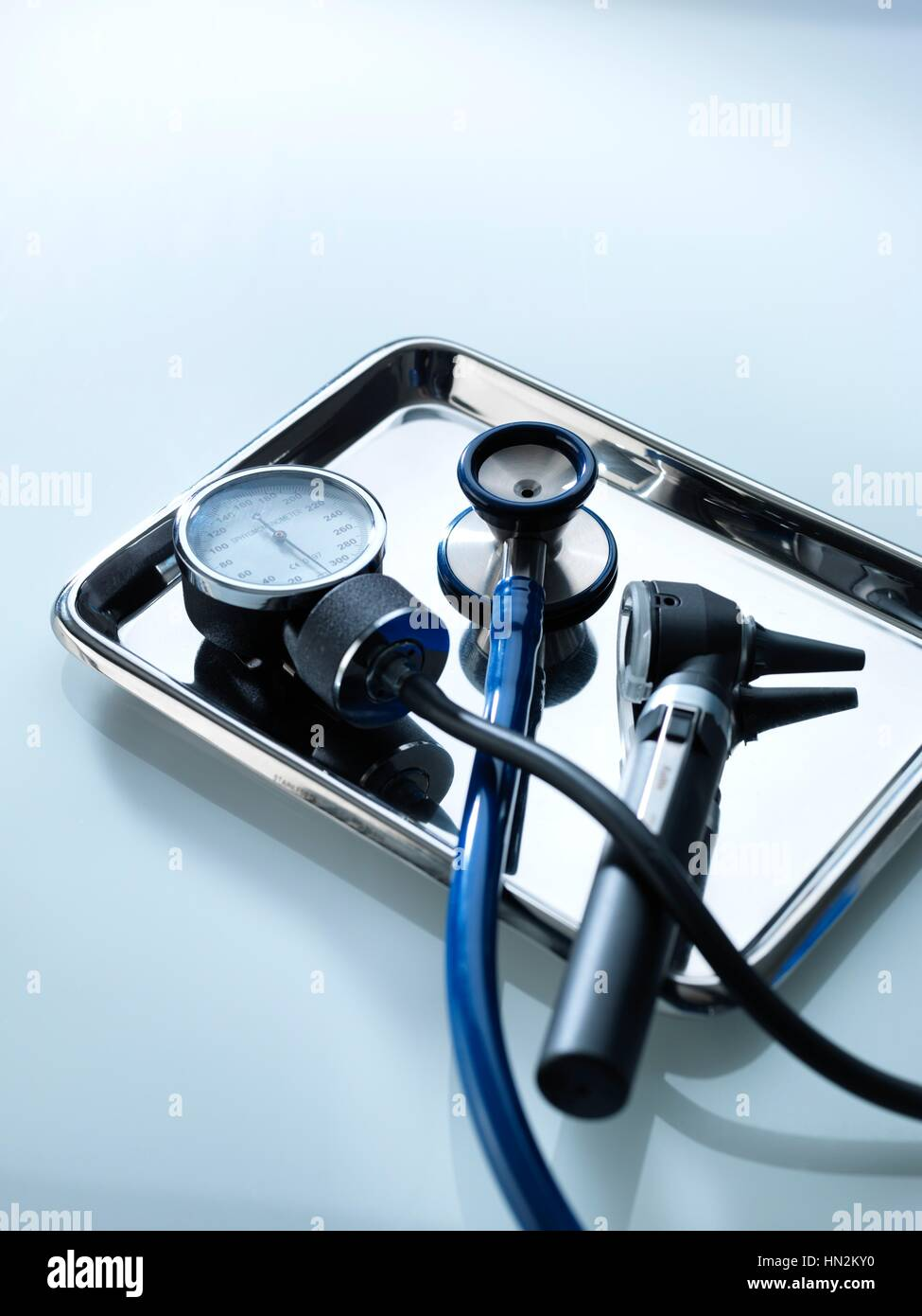 Sphygmomanometer, stethoscope and otoscope on a metal tray. - Stock Image