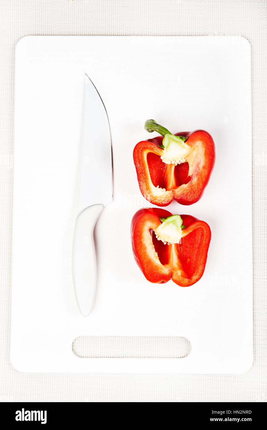 red sweet pepper and white knife on a white cutting board - Stock Image
