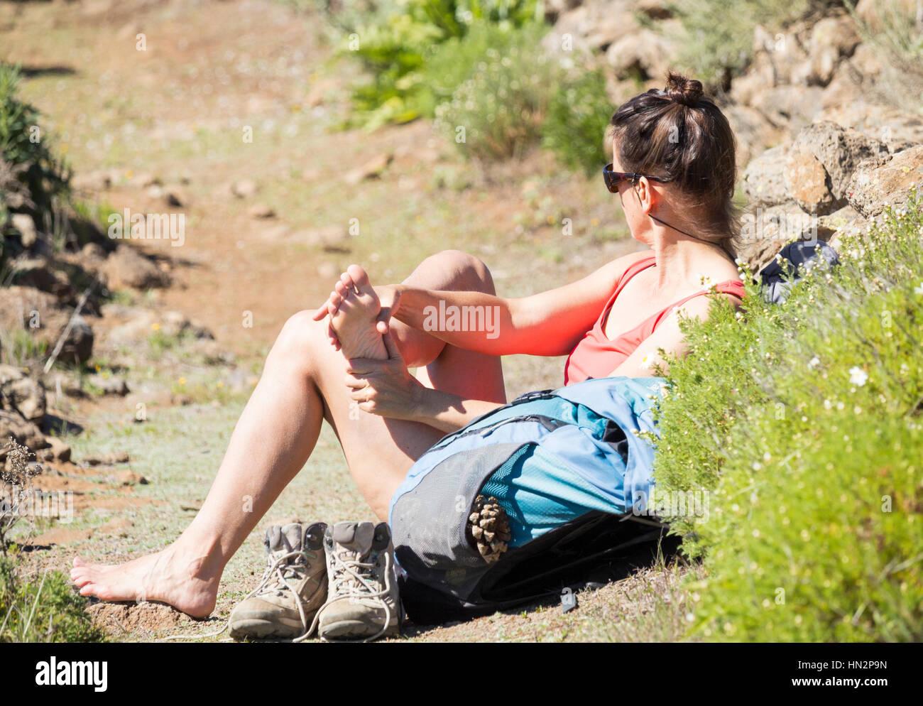 Foot massage, female hiker massaging her feet on mountain footpath. Stock Photo