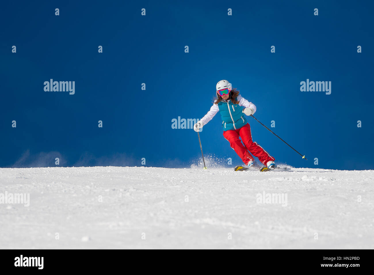 Woman Girl   Female Skier skiing downhill during sunny day i - Stock Image