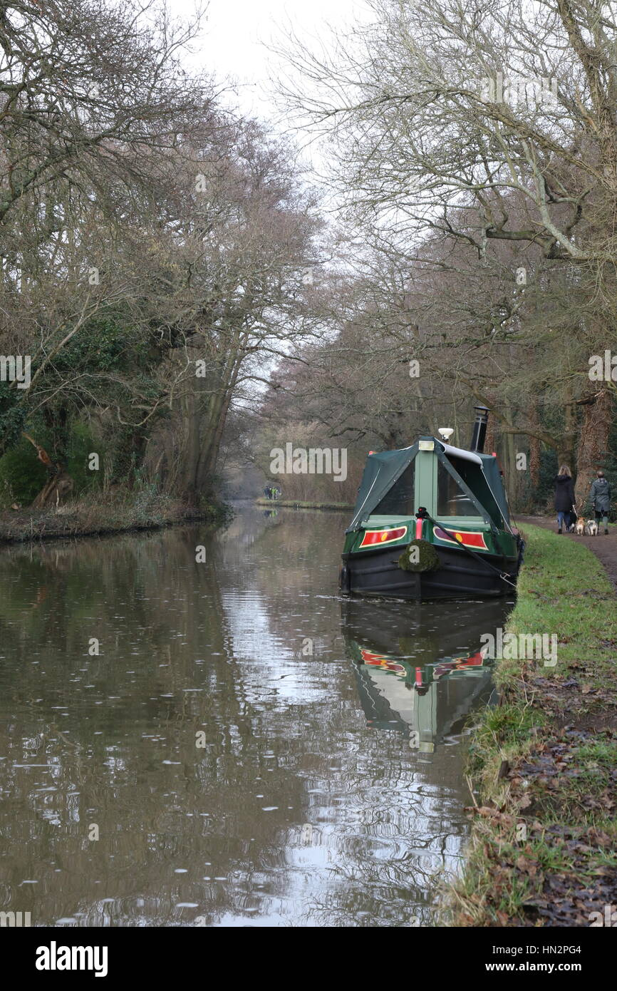 A houseboat barge moored to the towpath on the Wey Navigation Canal in Surrey - Stock Image