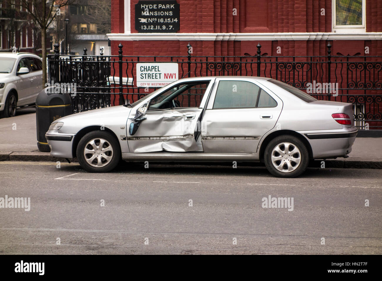 Damaged car parked at the side of the road, London, UK - Stock Image