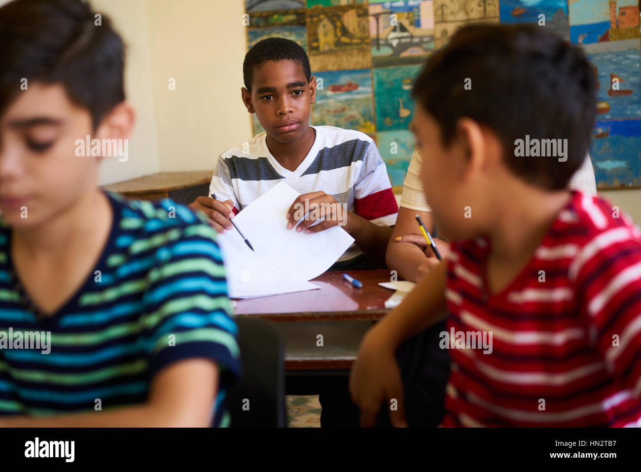 Young people and education. Group of hispanic students in class at school during lesson. Frustrated boys cheating - Stock Image