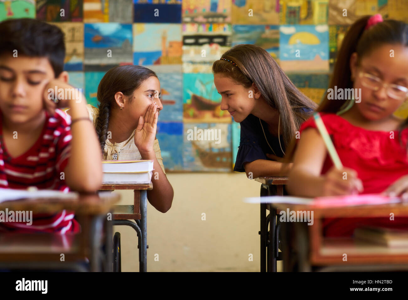 Young people and education. Group of hispanic students in class at school during lesson. Girls cheating during admission - Stock Image