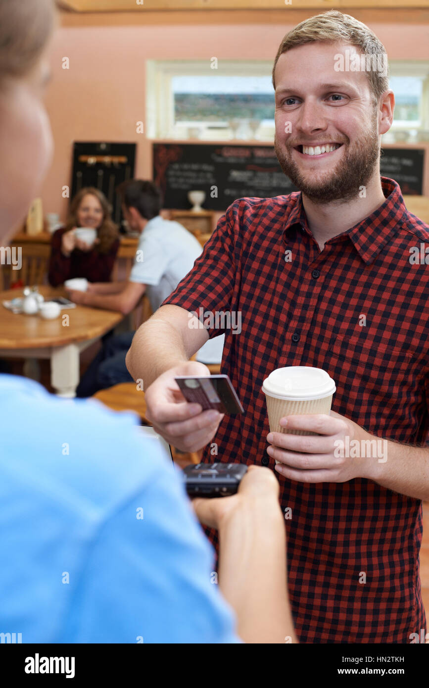 Customer Paying For Takeaway Coffee Using Contactless Terminal - Stock Image