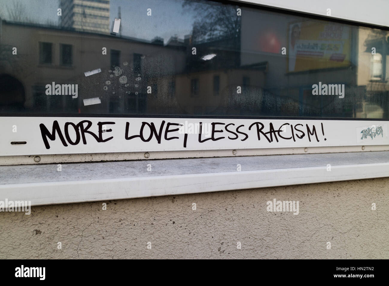 Graffiti on a building says More Love, Less Racism - Stock Image