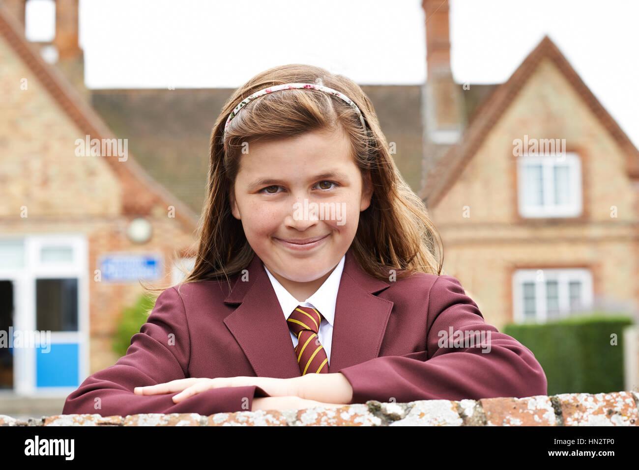 Portrait Of Girl In Uniform Outside School Building - Stock Image