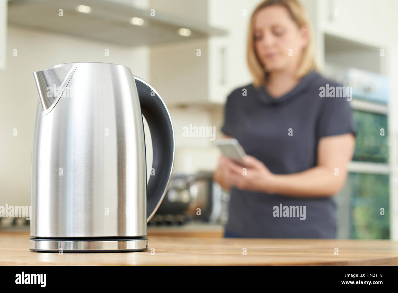 Woman Controlling Smart Kettle Using App On Mobile Phone - Stock Image
