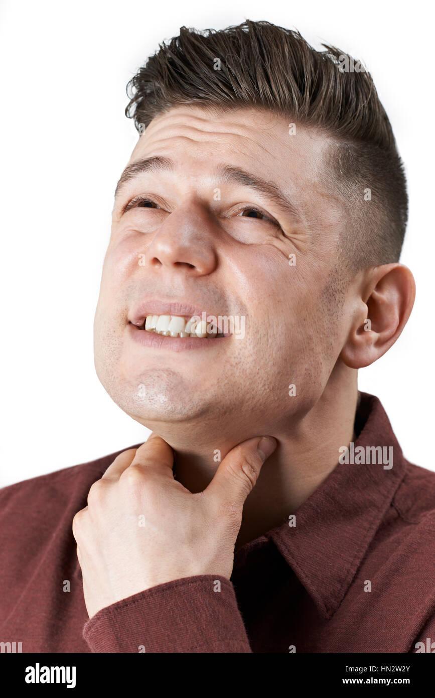 Studio Shot Of Man Suffering From Sore Throat - Stock Image