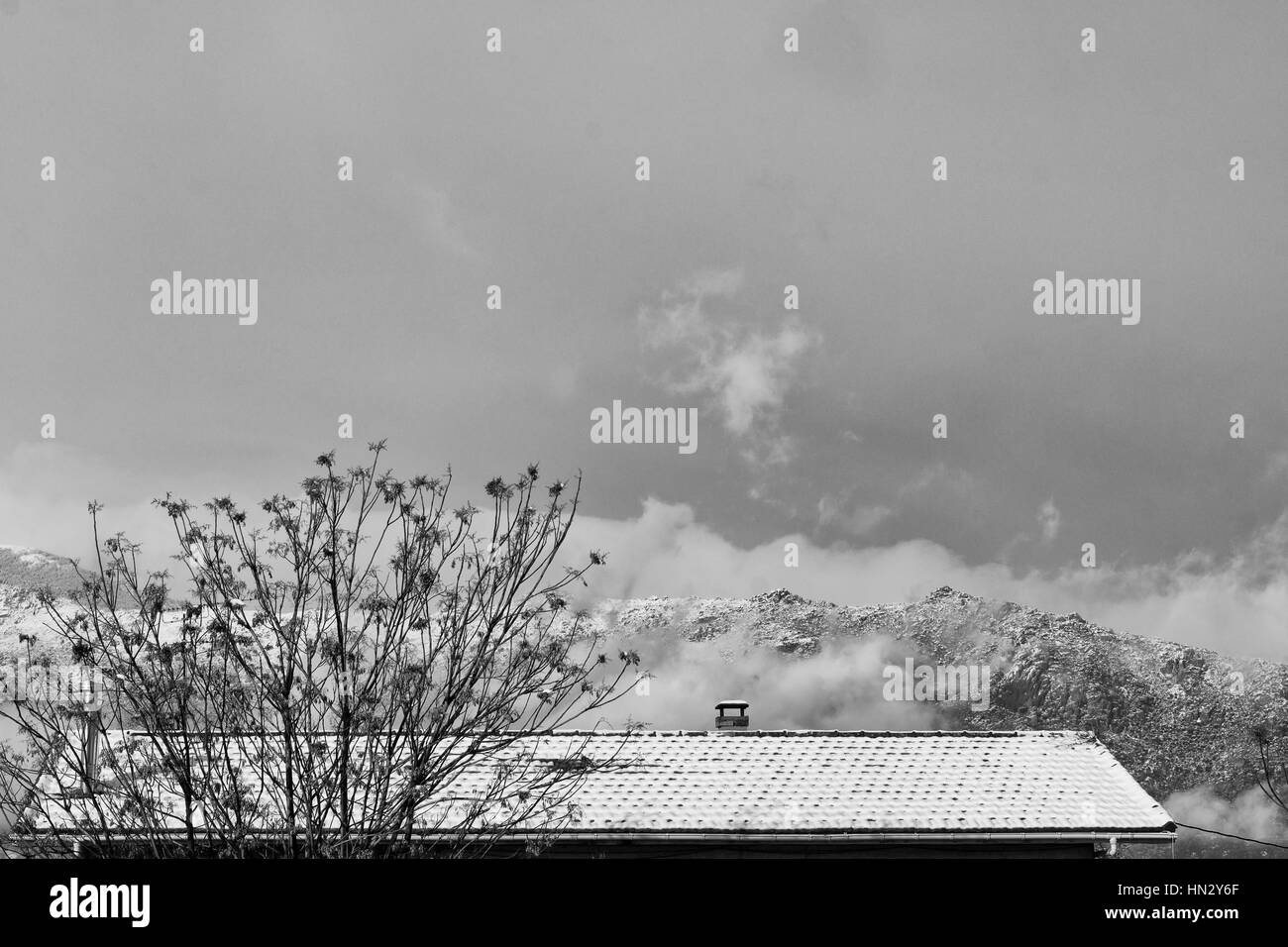 Snowy roof against background mountains in winter time. Subject captured over snow storm - Stock Image