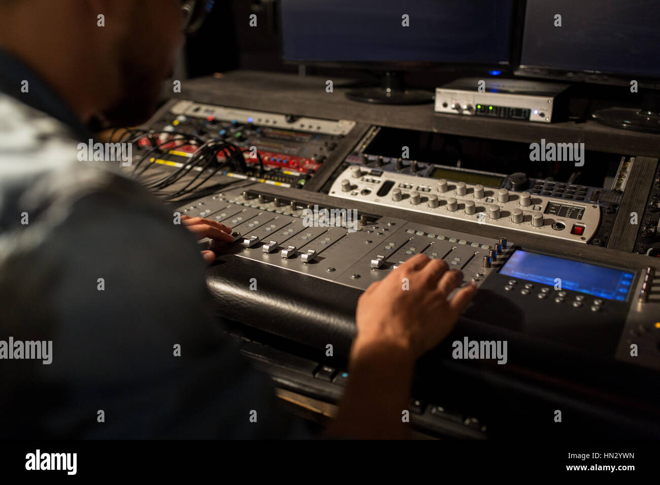 man using mixing console in music recording studio Stock Photo