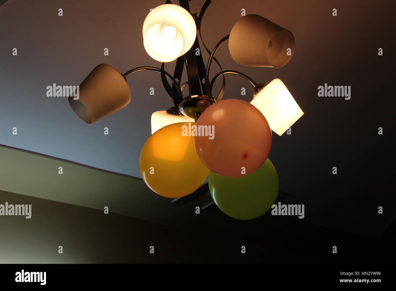 Chandelier with balloons and three illuminated bulbs - Stock Image