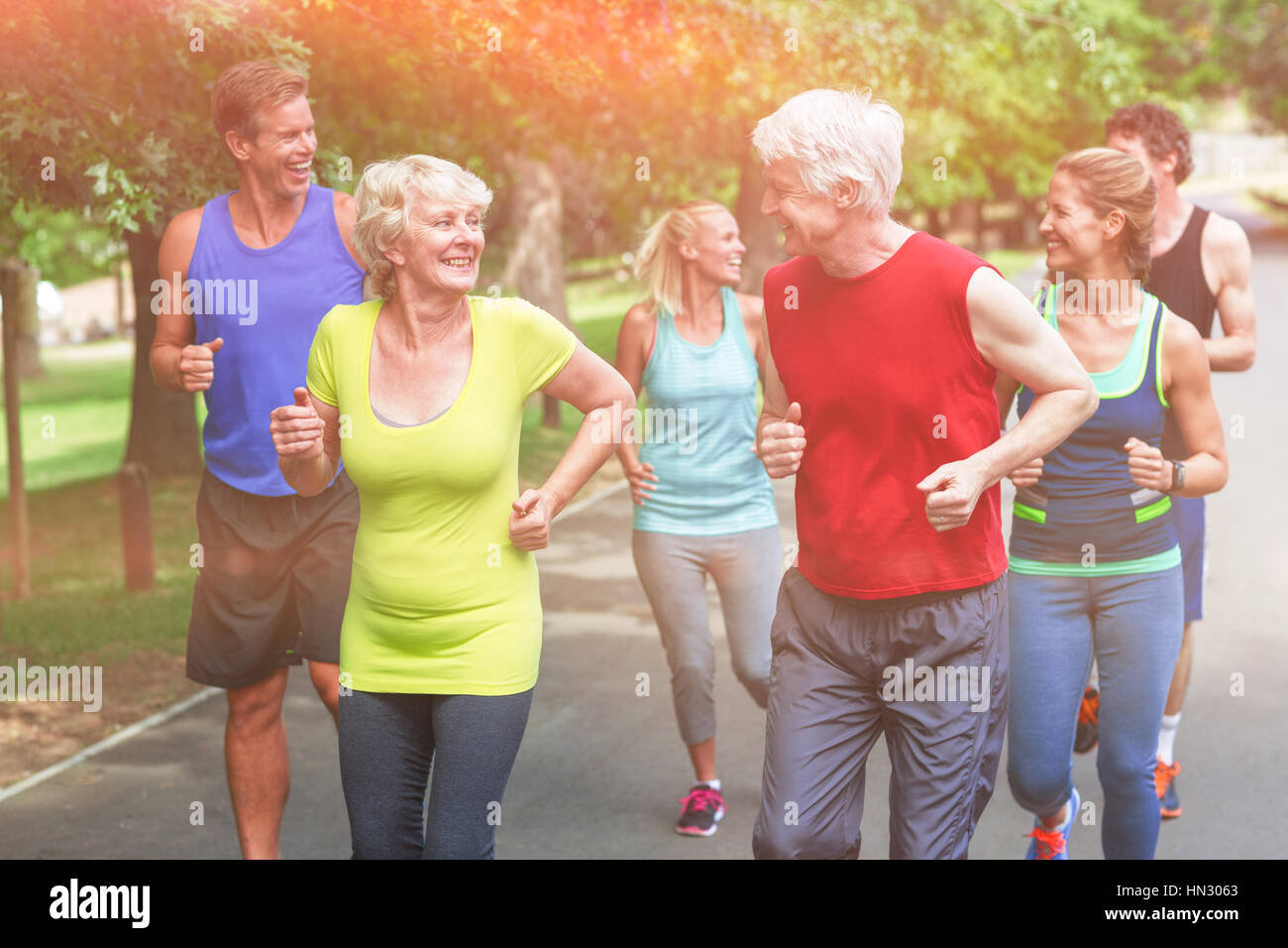 Marathon athletes running in park - Stock Image