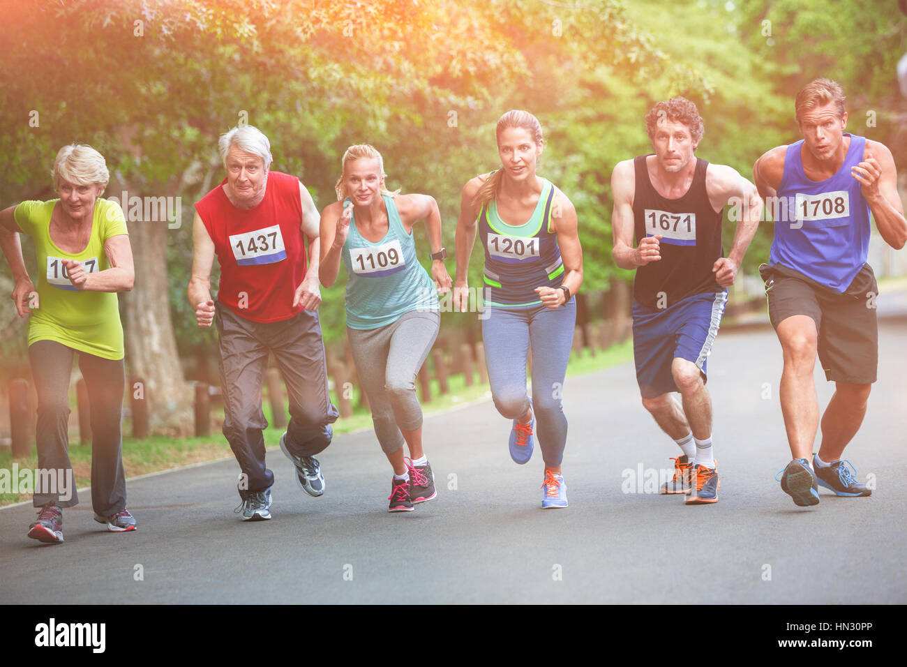 Marathon athletes on starting line in park - Stock Image