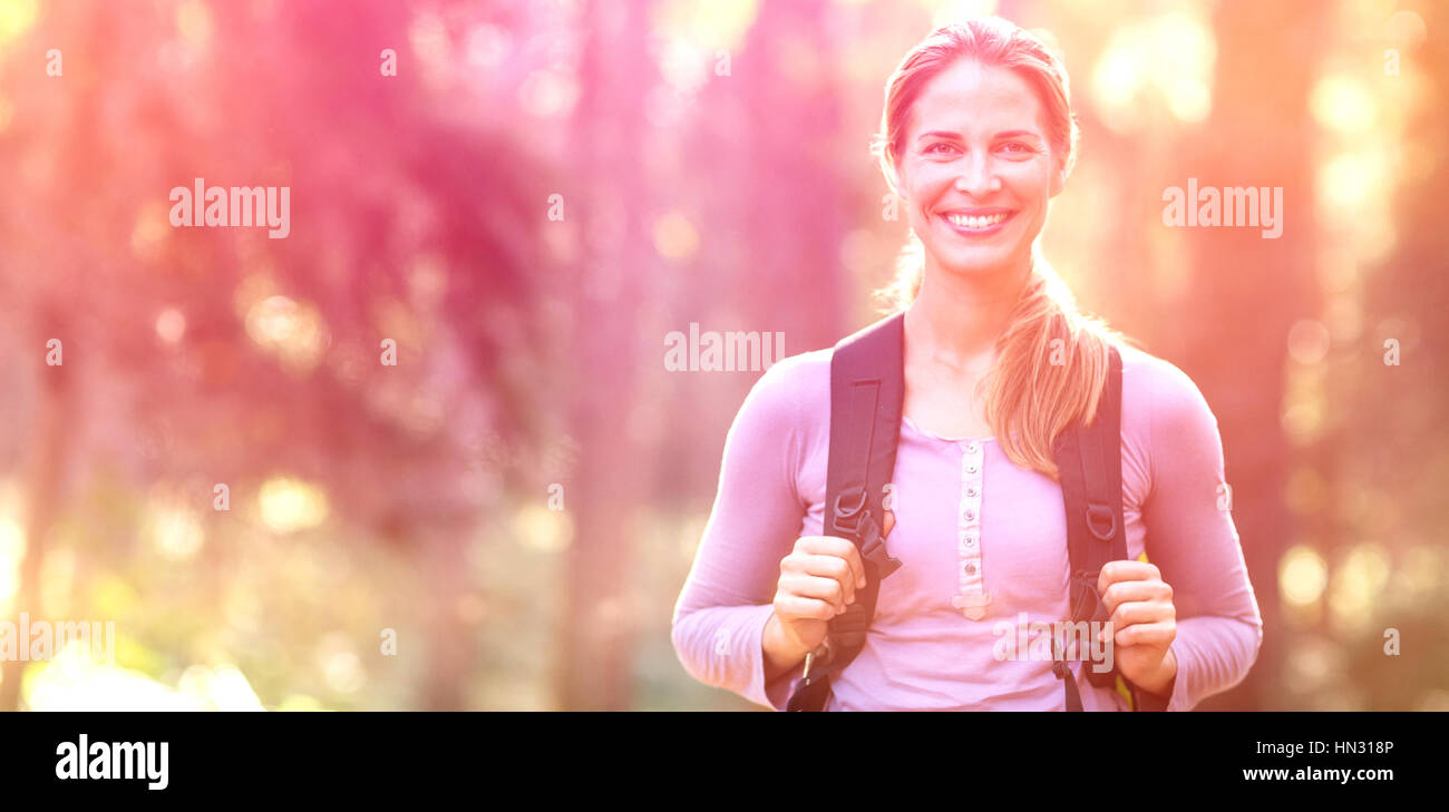 Portrait of smiling woman standing in forest carrying backpack - Stock Image