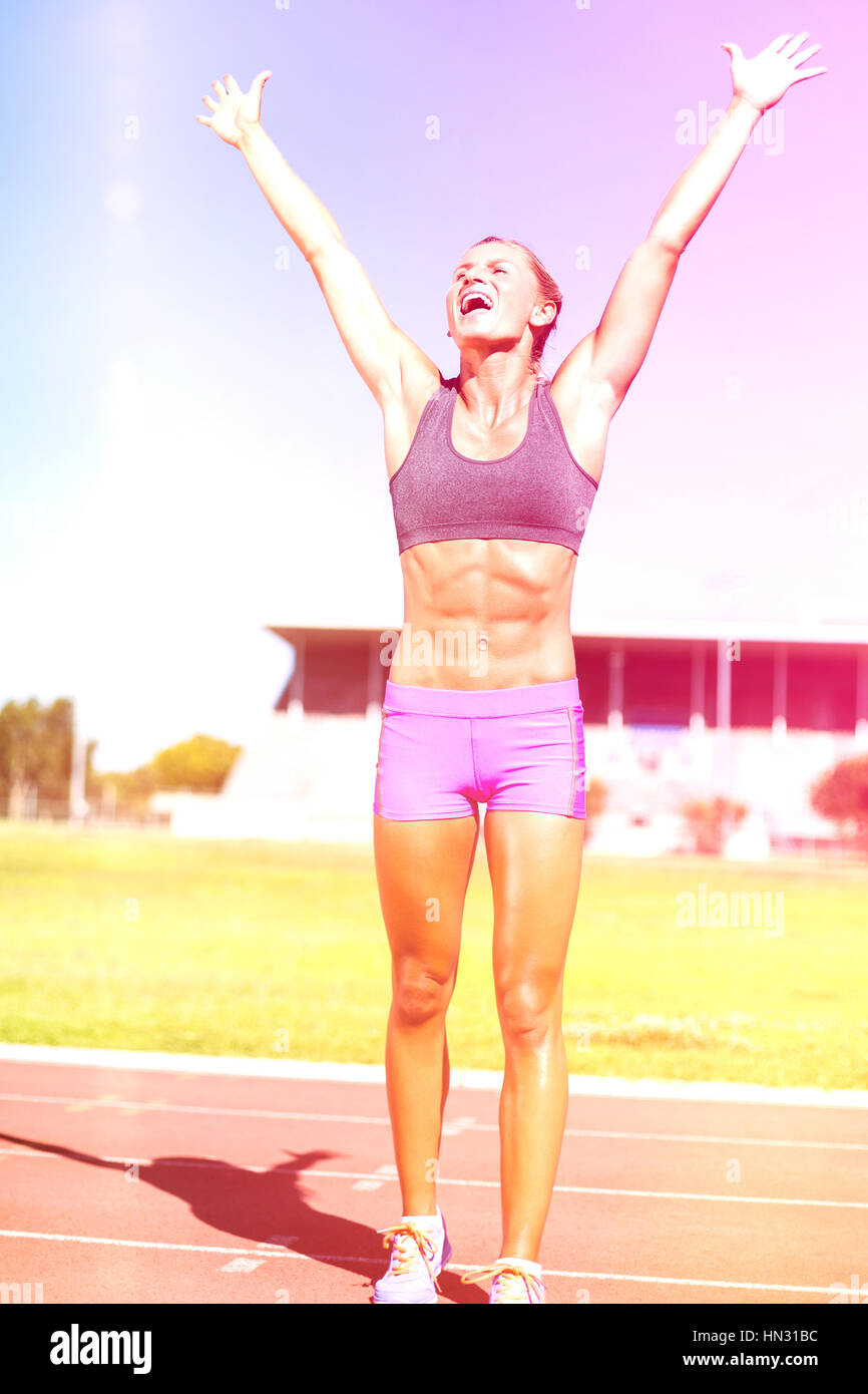 Excited female athlete posing after victory on racing track - Stock Image