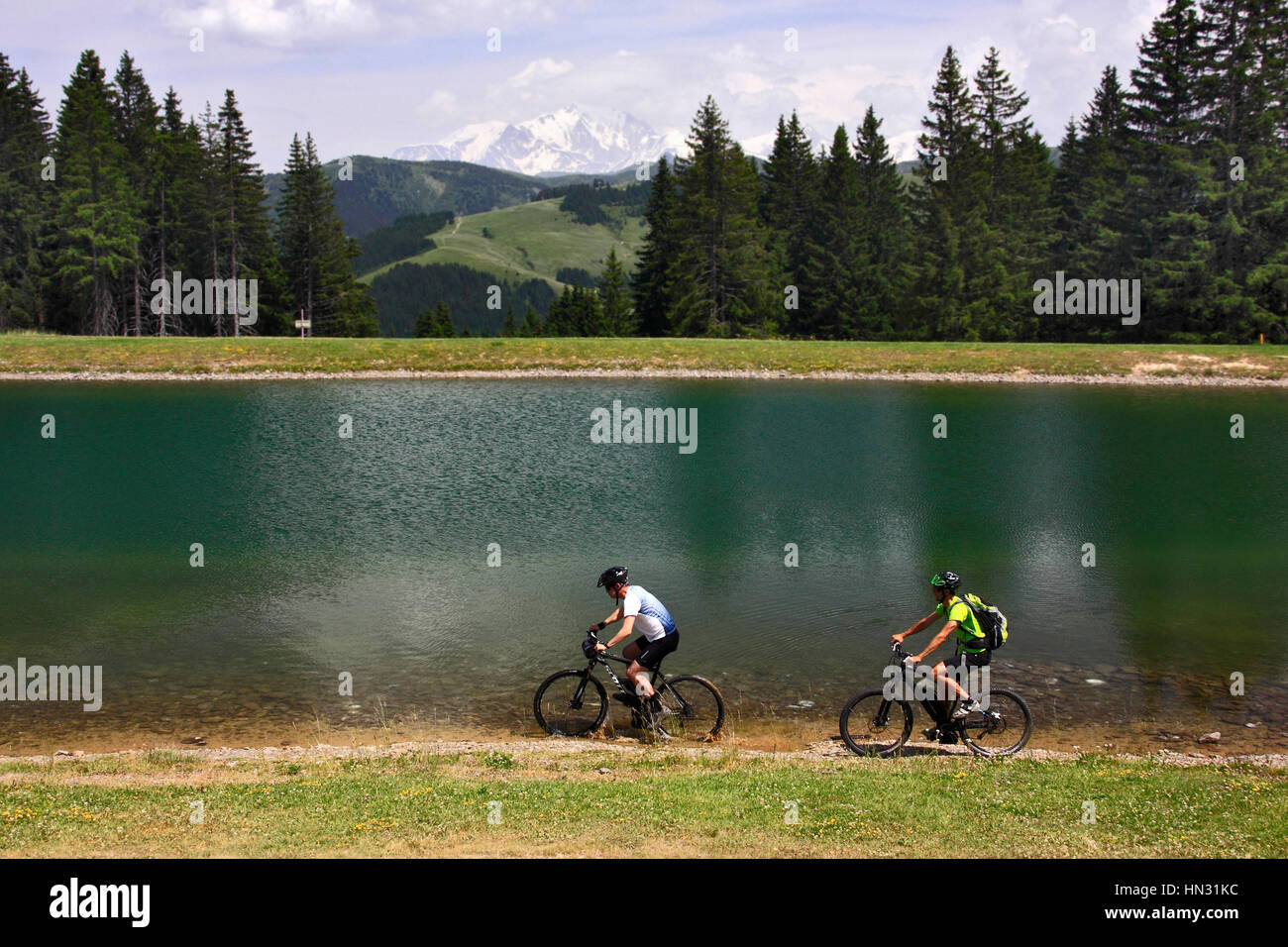 Two mountain bikers riding along lake with the mountain Mont Blanc in the background, French Alps, France - Stock Image